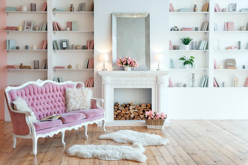 Modern light interior with fireplace, spring flowers and cozy pink sofa.  stock photography