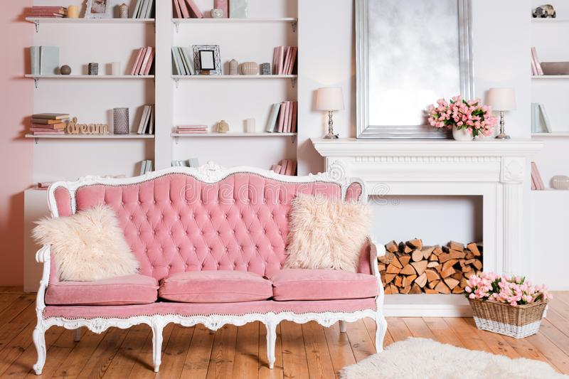 Modern light interior with fireplace, spring flowers and cozy pink sofa.  royalty free stock photography