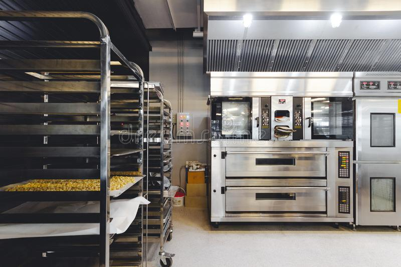 Modern pastry kitchen decorated in black, white and steel with baking machine, oven, conveyor, production line, mixer. Modern pastry kitchen decorated in black stock photos