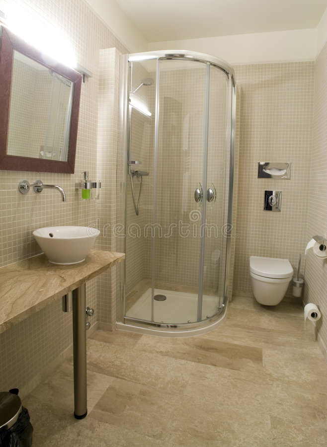 Modern shower and toilet. A picture of the interiors of a modern bathroom, with shower stall, toilet, sink and mirror. Decorated in a beige colour scheme royalty free stock photo