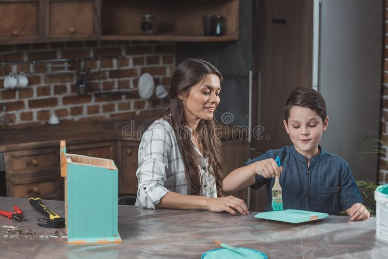 Little son and his beautiful mother sitting at table in kitchen and painting part of. Wooden birdhouse stock photo