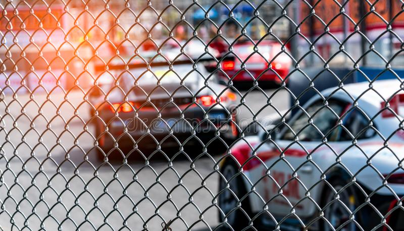 Motor sport car racing on asphalt road. View from the fence mesh netting on blurred car on racetrack background. Super racing car. On street circuit. Automotive royalty free stock images