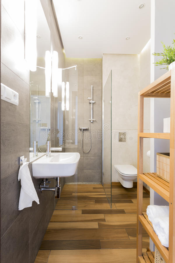 Narrow loft bathroom with wooden floor. Wooden floor in little inspiring loft design bathroom royalty free stock image