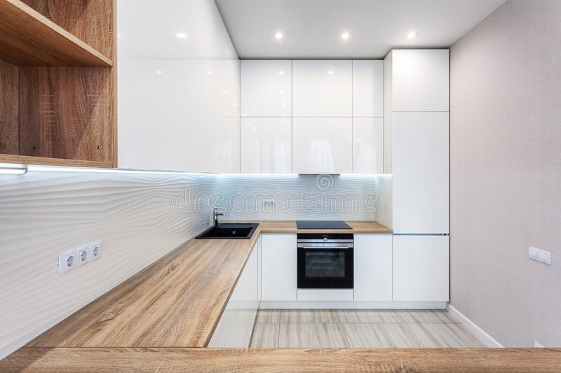 New bright modern kitchen with built in oven and chrome water tap and a wooden table top. stock photo