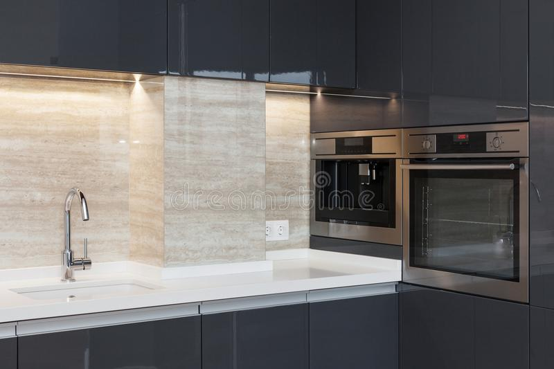New modern kitchen with built in oven and chrome water tap. LED worktop illumination. New modern kitchen with built in oven and chrome water tap. LED worktop stock image