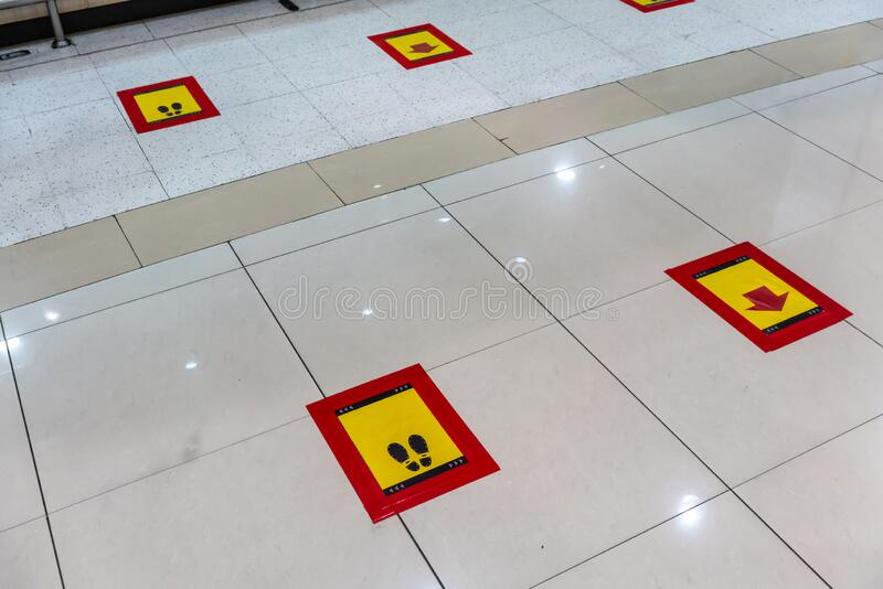 New normal social or physical distancing sign or standing mark on ground floor stock photography