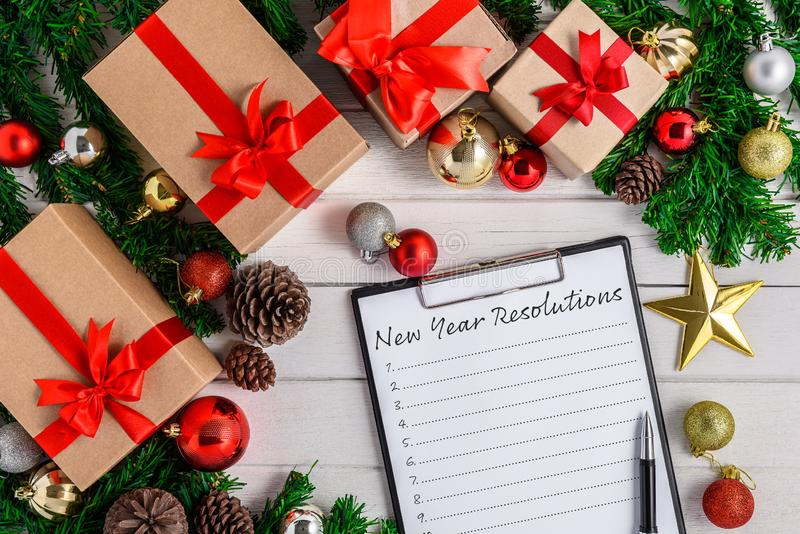 New Year`s Resolutions List written on white paper on clipboard with Christmas fir tree and decoration royalty free stock photography