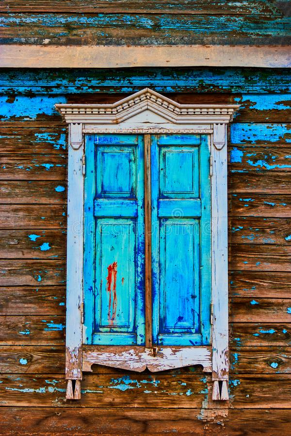 Obsolete window painted in worn blue color stock photography