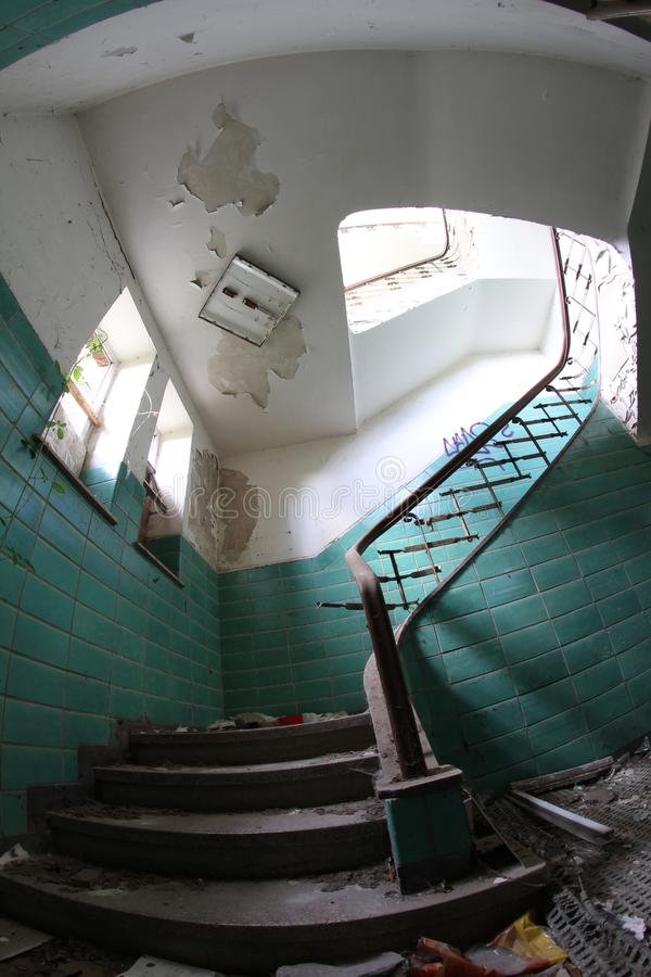 Old broken staircase with turquoise tiles, stone stairs and metal railing with wooden handrail. Several floors house. 