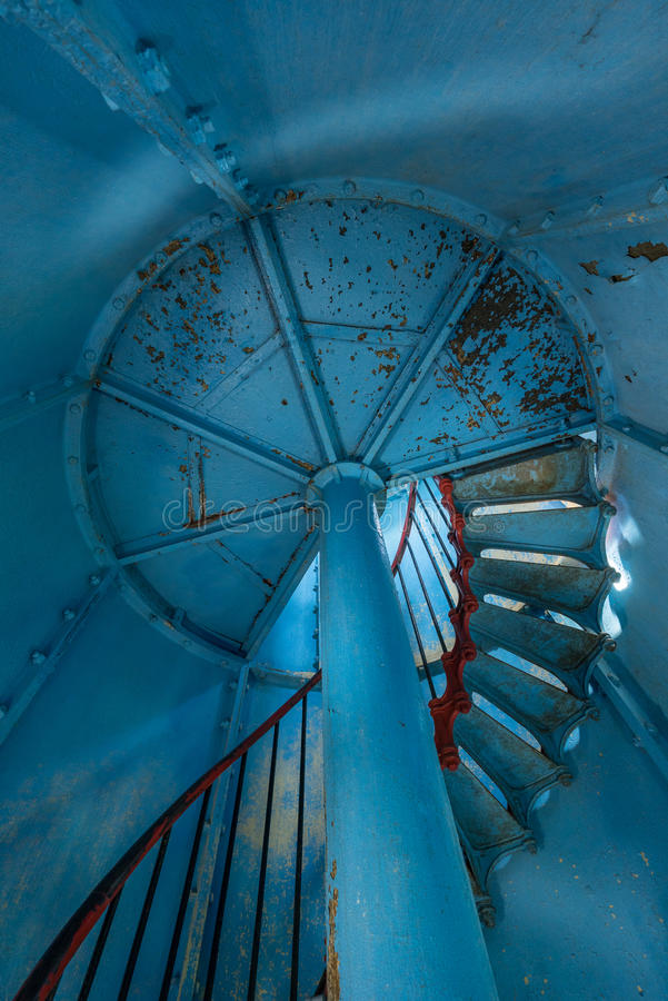 Old lighthouse on the inside. Red iron spiral stairs, round window and blue wall. Kihnu, small island in Estonia. Europe stock images