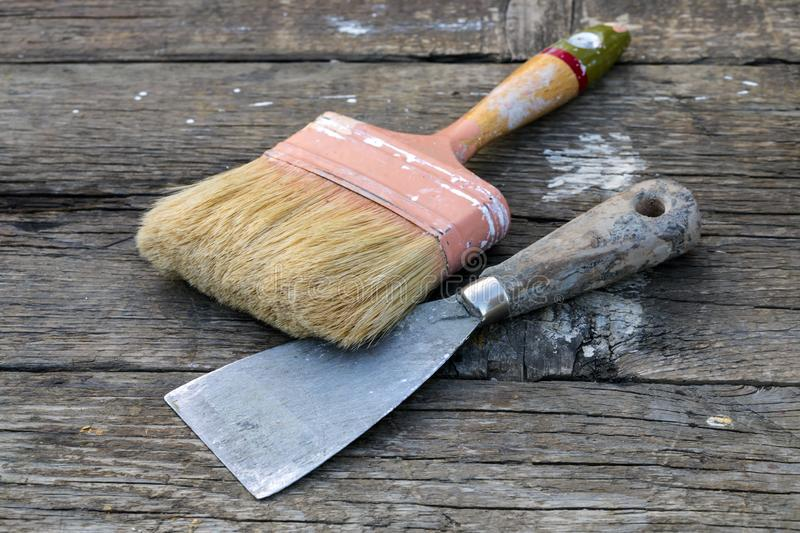 Old Paintbrush and Spatula. Old paintbrush and metal spatula on rustic wooden table stock photos