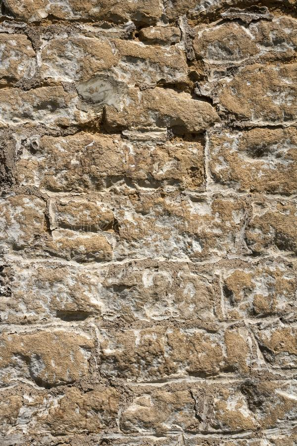 Old weathered exterior stone wall construction full frame background. An old previously painted weathered stone wall needs repairs. Construction full frame royalty free stock photo