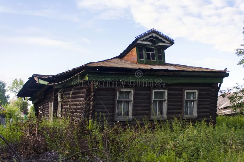 Old rickety wooden hut pimped in a Russian village. In summer under a blue sky stock photography