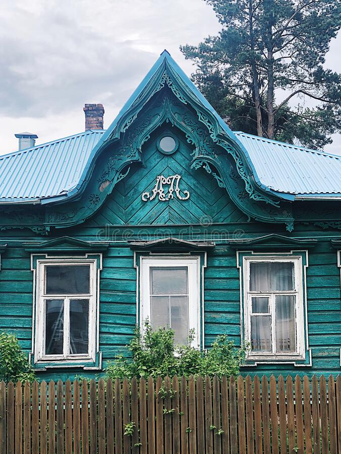 An old Russian hut with carved platbands. Blue mint house. Russian mood stock images