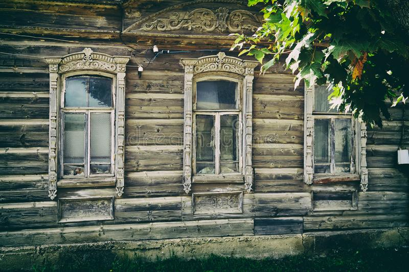 Old russian traditional wooden house facade with carved windows stock photo