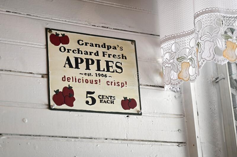 Retro Apple Advertisement. An old sign in a fruit market with lace curtain and clapboard walls advertises crisp delicious apples for sale royalty free stock photo