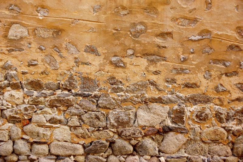 Old Stone Wall Made From Granite Rocks And Ripped Plaster royalty free stock image