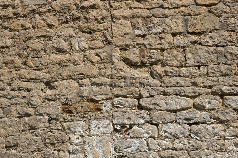 Old weathered exterior stone wall construction full frame background. An old weathered stone wall needs repairs. Construction full frame texture background stock images