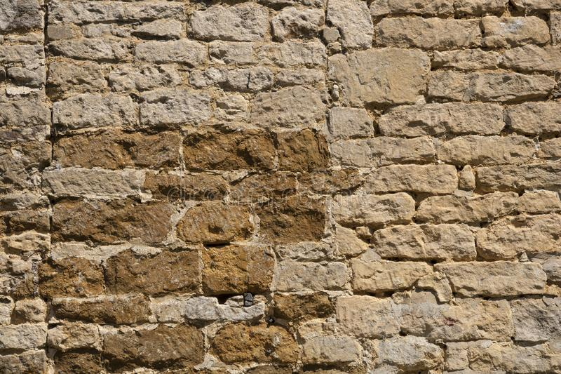 Old weathered exterior stone wall construction full frame background. An old weathered stone wall needs repairs. Construction full frame texture background stock photo