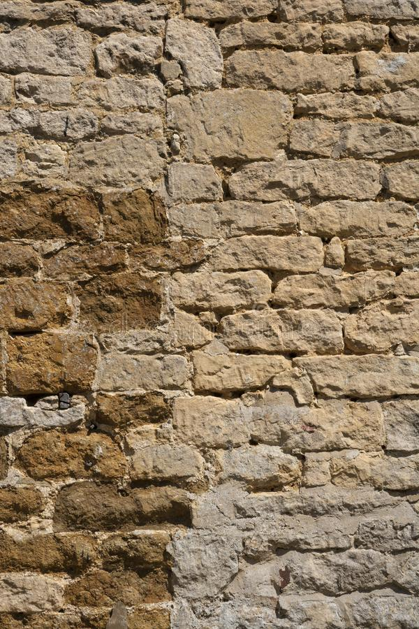 Old weathered exterior stone wall construction full frame background. An old weathered stone wall needs repairs. Construction full frame texture background royalty free stock images