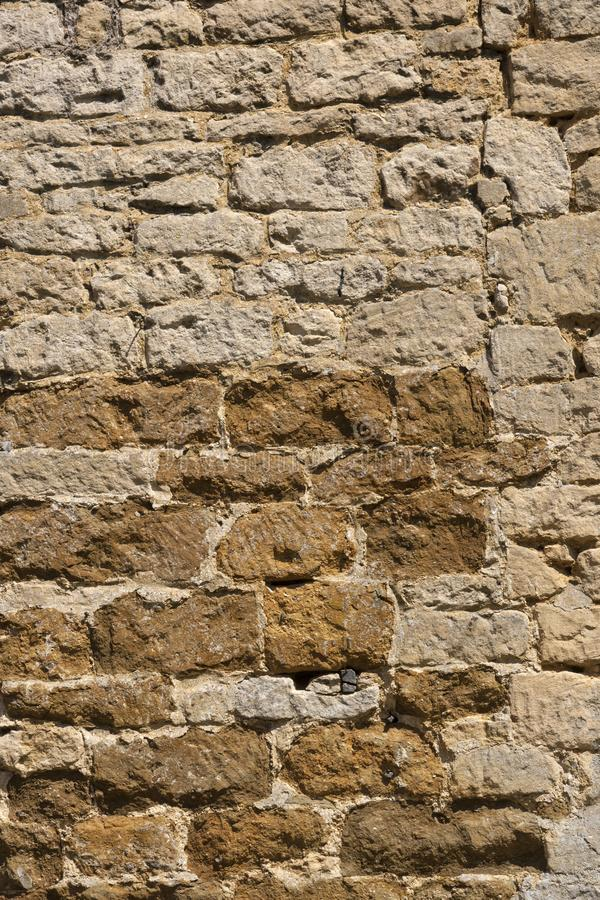 Old weathered exterior stone wall construction full frame background. An old weathered stone wall needs repairs. Construction full frame texture background stock photography