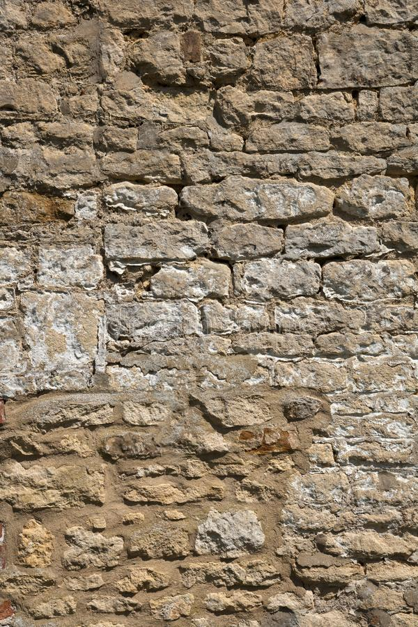 Old weathered exterior stone wall construction full frame background. An old weathered stone wall needs repairs. Construction full frame texture background royalty free stock image