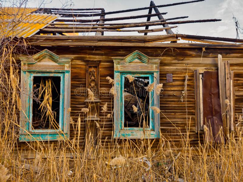 Old wooden hut in russian style half abandoned with reed growing all about. Weathered wooden hut in russian style half abandoned with reed growing all about royalty free stock image