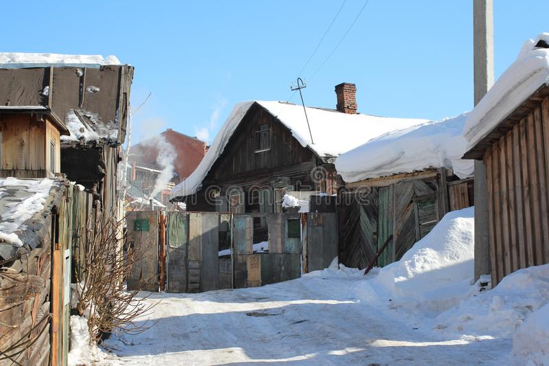 Old wooden village house with outbuildings in the winter. In Russia stock image