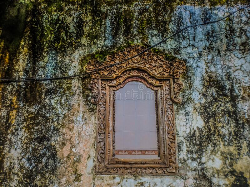 Ornate carved window frame in dilapidated and mossy wall royalty free stock photos