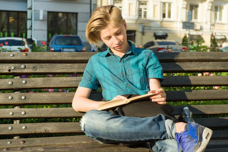 Outdoor portrait of a teenage boy and girl 14, 15 years old, sitting on bench in city park with book. Outdoor portrait of a teenage boy and girl 14, 15 years royalty free stock images