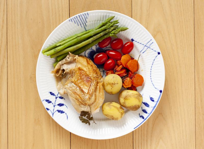 Oven-roasted chicken with plum tomatoes, new potatoes and green asparagus on a plate. Top view on wooden background. - Image royalty free stock photo