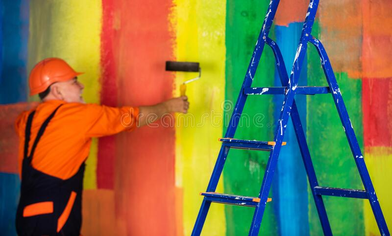 Painter man staircase. To make repairs. man in working clothes painting wall in empty room. painter in overall and cap royalty free stock photography