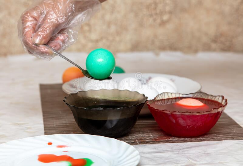Painting eggs in the kitchen. Orthodox Easter holiday stock images