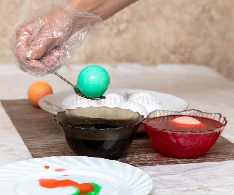 Painting eggs in the kitchen. Orthodox Easter holiday royalty free stock image