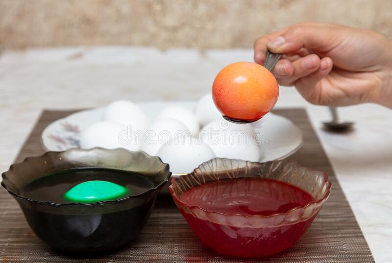 Painting eggs in the kitchen. Orthodox Easter holiday royalty free stock photography