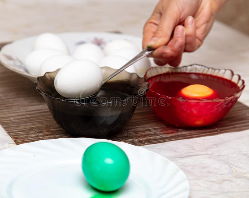 Painting eggs in the kitchen. Orthodox Easter holiday stock image