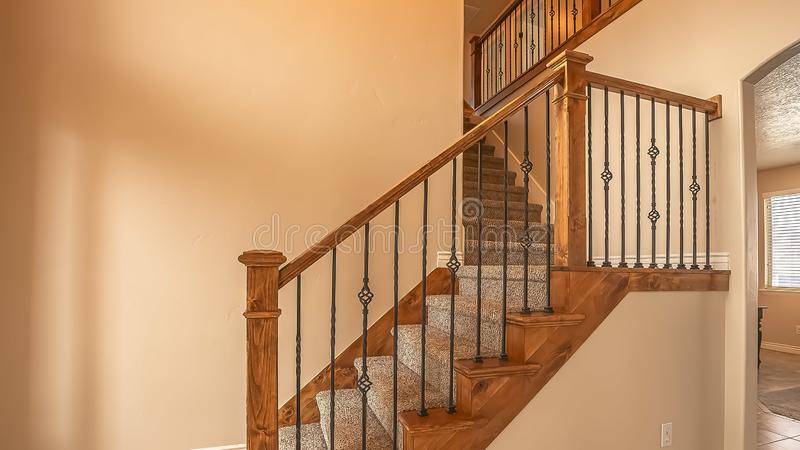 Panorama frame Carpeted stairs with wood handrail and metal railing inside an empty new home. Beige wall, shiny floor, window with blinds, and arched doorway royalty free stock images