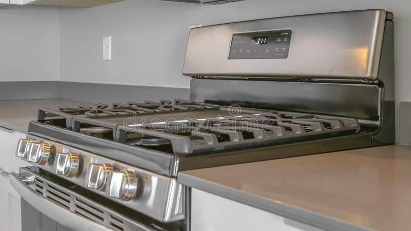 Panorama frame Range with cooktop and oven inside the modern kitchen of a new house. A microwave is mounted on the wall above the shiny cooking range stock photography