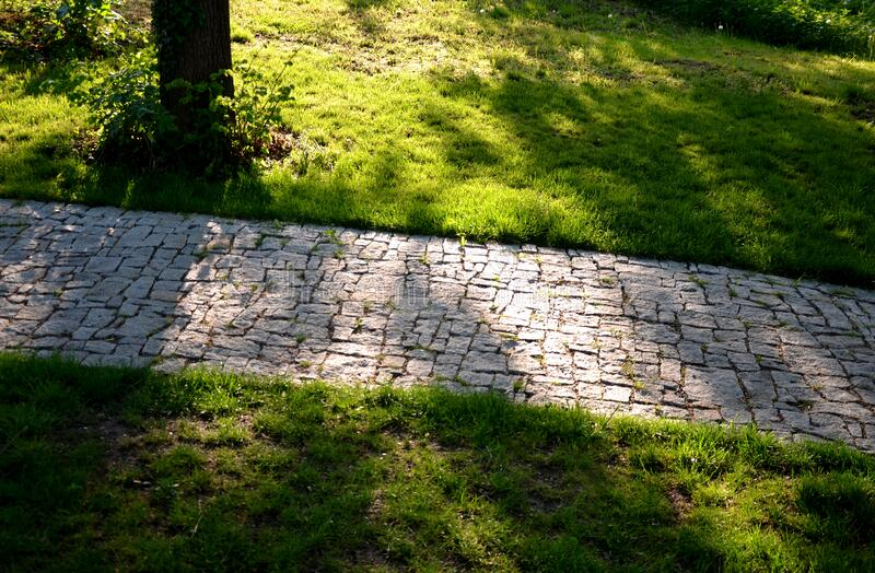Granite paving of irregular sections of chipped stone around a park with green lawn gray color of the pedestrian path. Path, nature, stone, garden, green, forest royalty free stock photo