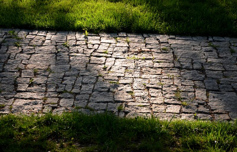 Granite paving of irregular sections of chipped stone around a park with green lawn gray color of the pedestrian path. Path, nature, stone, garden, green, forest royalty free stock images