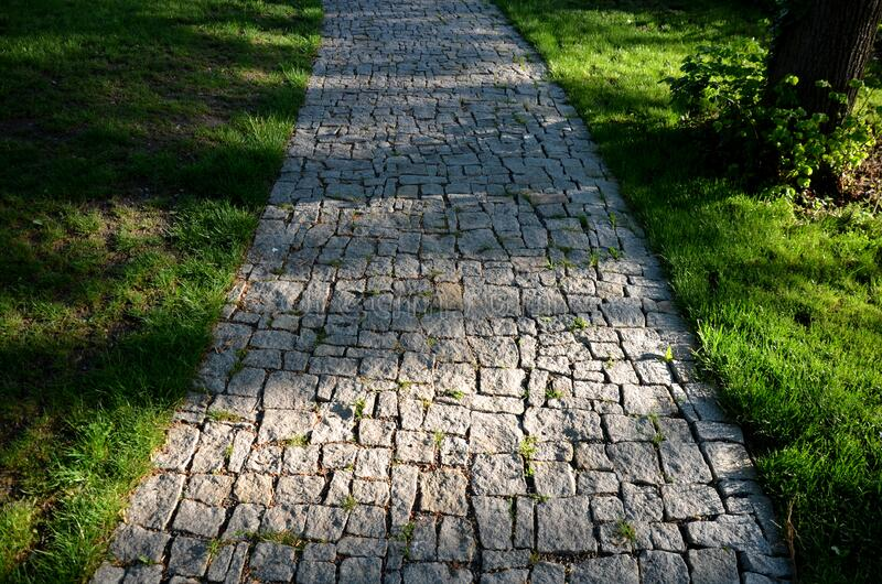 Granite paving of irregular sections of chipped stone around a park with green lawn gray color of the pedestrian path. Path, nature, stone, garden, green, forest stock image