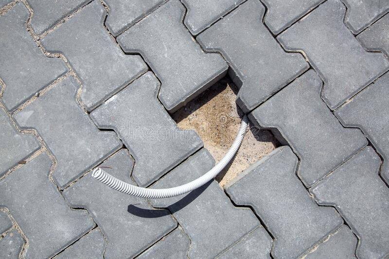 Pedestrian pavement made of gray  mosaic stone tiles with an opening for an electric cable. stock image