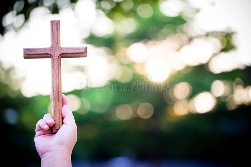 Person palm hands to hold holy cross, crucifix to worship. stock photography