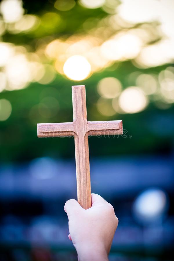Person palm hands to hold holy cross, crucifix to worship. royalty free stock image