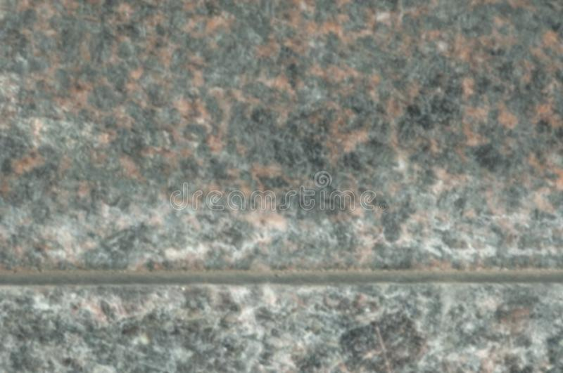 Stone finishing polished granite. Solid rock of a granular structure of quartz, feldspar and mica. The photo is not sharp, blurry in Gouse Stone finishing royalty free stock image