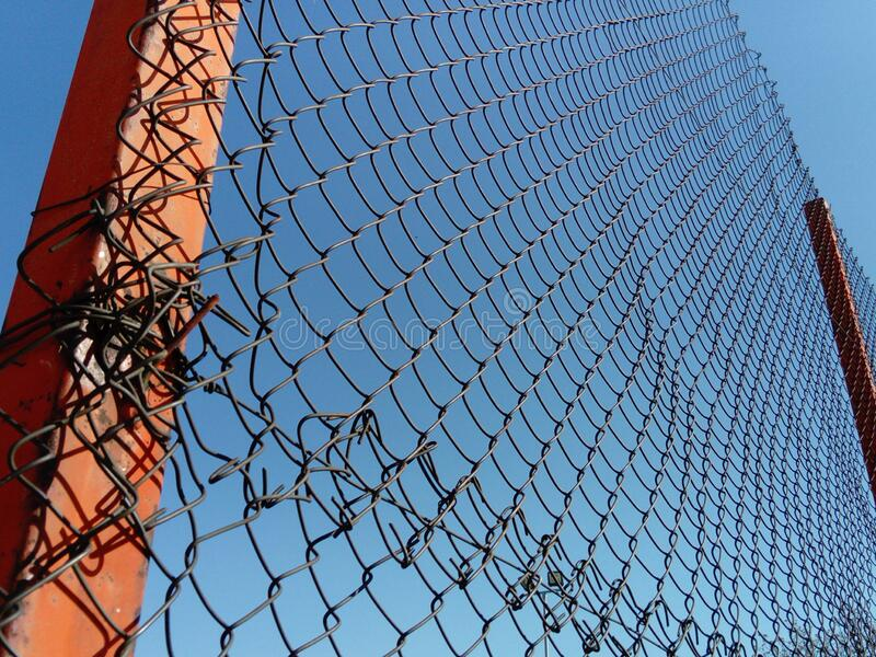 Plexus wire. Metal mesh netting attached to a pole. Part of the fence on the sports ground. In the background is a blue sky. The picture is from below stock image