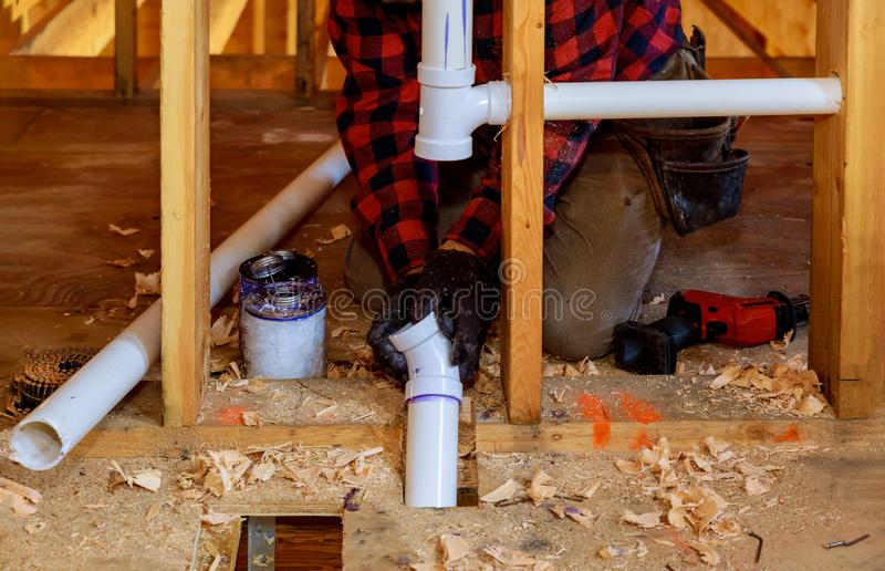 Plumber putting glue on a PVC drain pipe, closeup stock photography