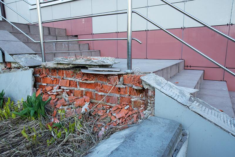 Crumbling brick porch needs repair. Poorly made repairs in the entrance, the entrance to the porch of the building and the stairs are destroyed, ceramic tiles royalty free stock image
