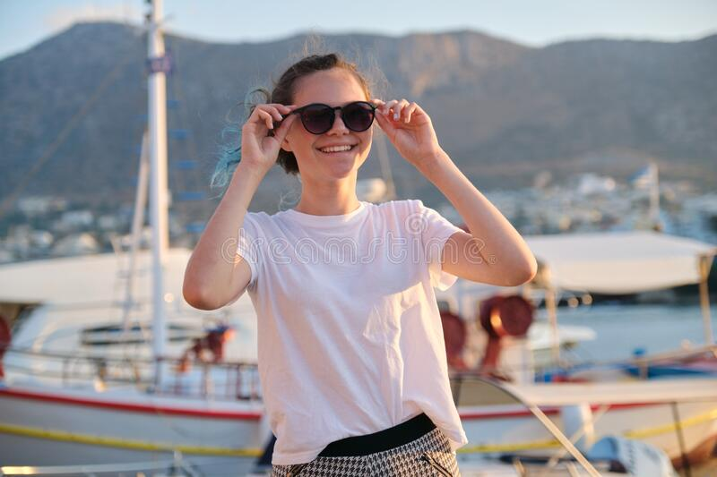 Portrait of teenage girl 15 years old, happy smiling teenager. Summer sunset sea harbor with yachts background. Vacation, adolescence, travel concept royalty free stock images
