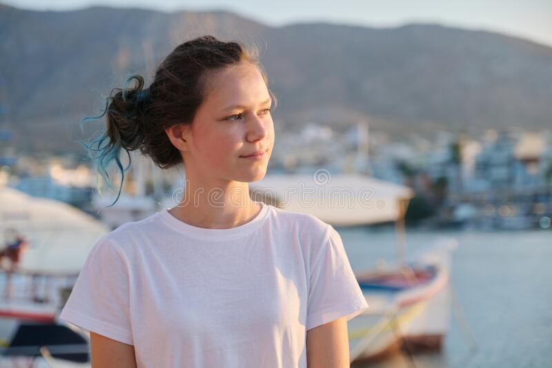 Portrait of teenage girl 15 years old, happy smiling teenager. Summer sunset sea harbor with yachts background. Vacation, adolescence, travel concept royalty free stock photo